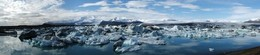 Panoramic image of glacial lagoon Jokulsarlon- Oraefi massif in background with Fjallsjokull draining the volcano on the left, and Breidamerkurjokull to the right, Iceland.